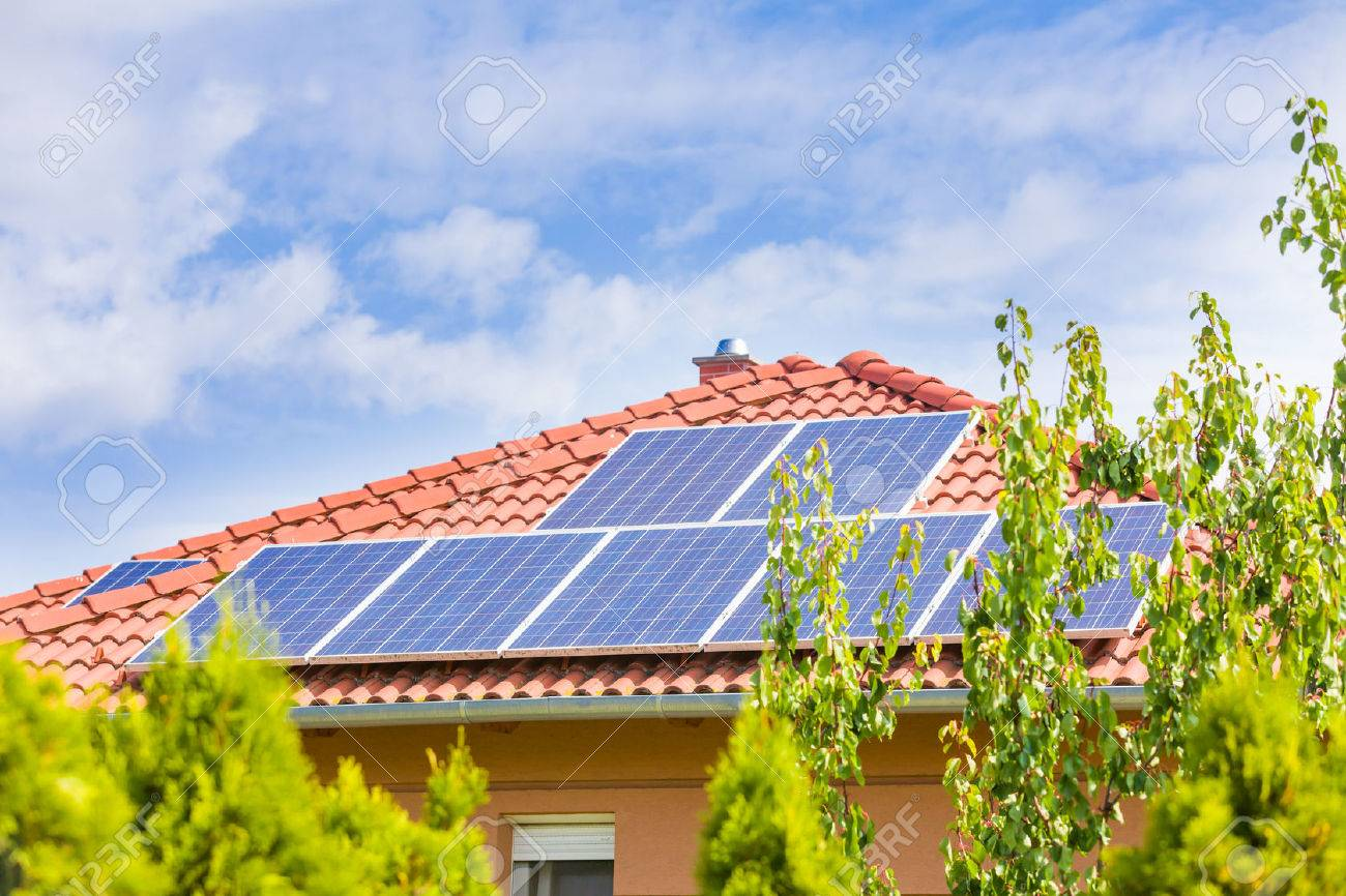 Triangular tile roof plane with solar panel array under blue sky with clouds.