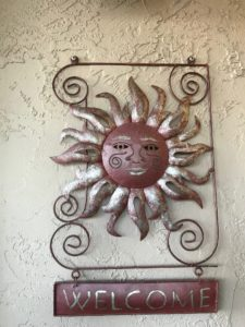 """Sun with face suspending a """"Welcome"""" sign"""