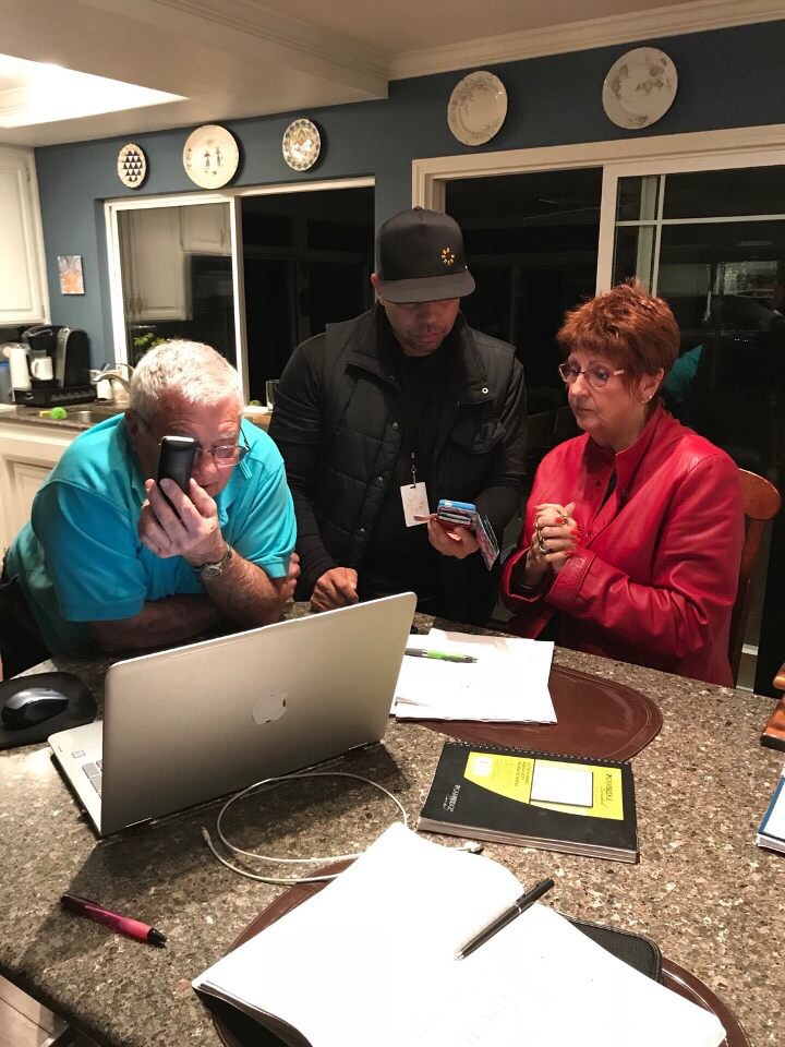 Richard on phone next to Mario of Sunstor Solar and Dianne looking at solar options