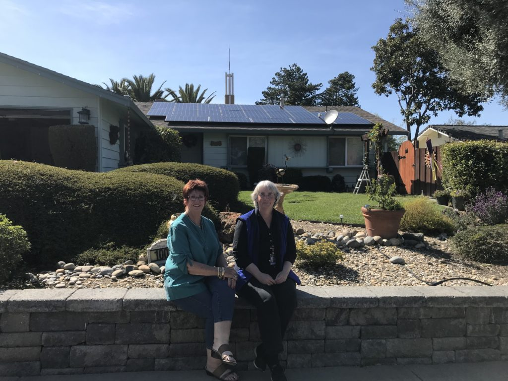 Sandra and Dianne seated on a wall in front of Dianne's house with solar